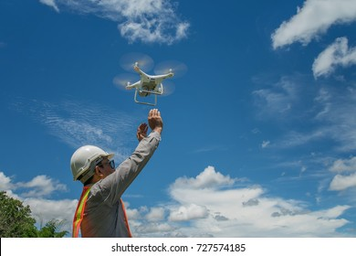 Young engineer use drones outdoor with beautiful sky with clouds, the man holding Drone