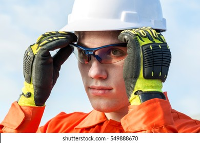 Young engineer is wearing safety goggles.