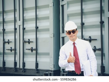 Young engineer wearing a white hat, red tie inspector holds thumb is happy with the work.