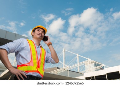 Young engineer wearing yellow helmet safety speaking on mobile phone look to sky in front construction building.