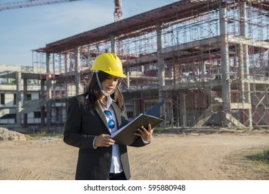 A young engineer woman is inspecting a construction site.