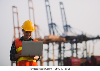 Young engineer woman standing wear safety helmet working with work by laptop evening time. blur background,