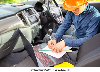 Young engineer working with laptop inside car. Helmet place on car seat