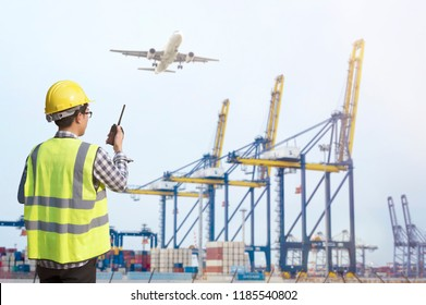 Young engineering man and safety helmet, shirts standing arms crossed against cargo port