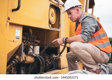 Young engineers inspected road construction vehicles in the construction site.