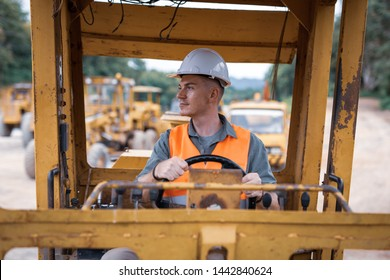 Young engineers are working on road construction vehicles, outdoor