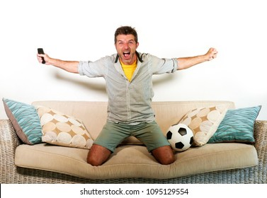 young enthusiastic football fan celebrating goal crazy happy jumping on sofa couch at home watching soccer game on television holding remote in goal celebration gesture