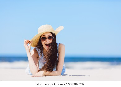 Young enthusiastic girl laying on the beach, smiling. Wow expression. Traveling. Summer.