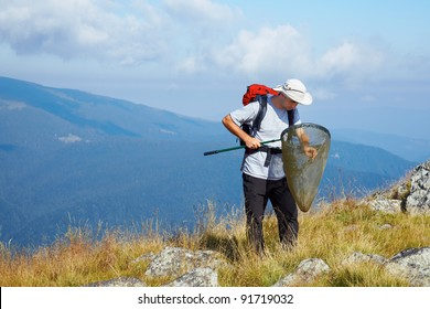 Young entomologist searching for insects at high altitude in the mountains.
