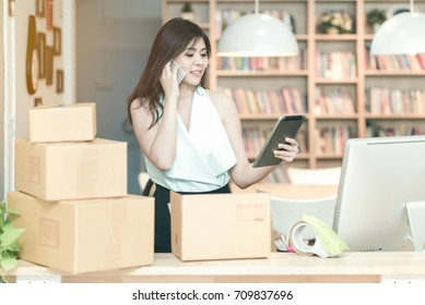 Young entrepreneur checking products stock on the smart tablet while talking to her customer at home office.Conceptual for startup small businesses starting own company and online marketing.
