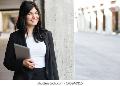 Young entrepreneur holding a tablet and smiling