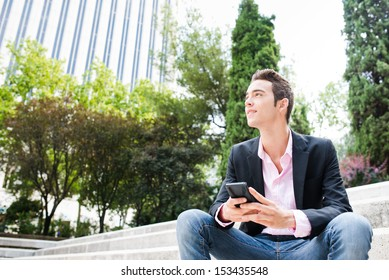 Young entrepreneur looking away and smiling sit on stairs. Focus on his face