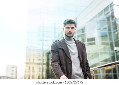 young entrepreneur looking confident, with office building behind him, looking relaxed. succesfull stylish man