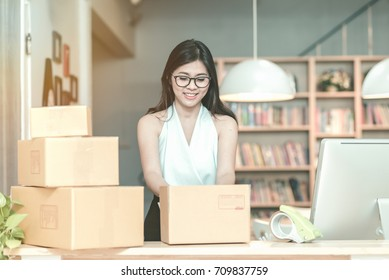 Young entrepreneur packing product into the box for her customers after received order at home office. Conceptual for startup small businesses starting own company and online marketing.