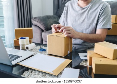 Young entrepreneur SME man receive order client and working with packaging sort box delivery online market on purchase order and preparing package product, Small business parcel for shipment.