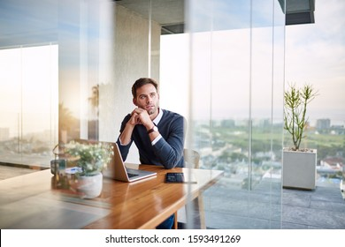 Young entrepreneur thinking up new ideas while working on a laptop at a table at home