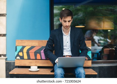 Young entrepreneur working on laptop, sitting on wooden bench near cafe window on the street with cup of coffee. Freelancer, in casual jacket, unbuttoned shirt, jeans typing looking to laptop screen.