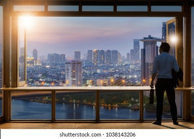 Young entrepreneurial vision, casual wear, luggage, work in the office near glass windows and look through modern buildings.