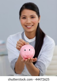 Young ethnic businesswoman saving money in a piggybank in the office