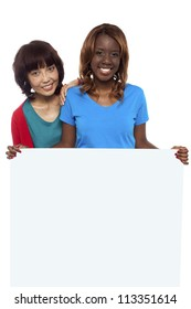 Young ethnic friends behind blank ad board smiling at camera