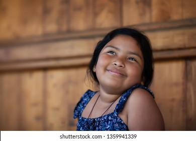 Young ethnic girl remembering a happy moment in her mind and expressing joy through a smile and bright eyes.