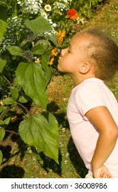 Young Ethnic Girl smelling the flowers in the garden.