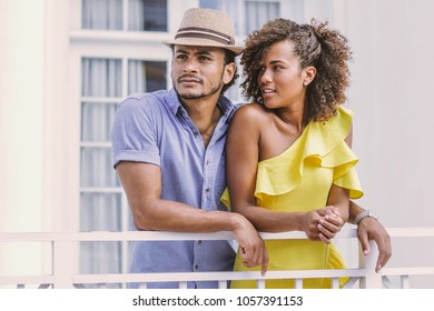 Young ethnic handsome man and pretty woman in yellow dress standing together at handrail on the street.