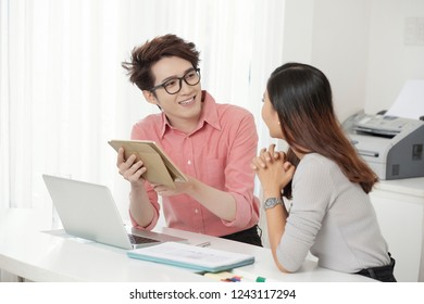 Young ethnic man and woman coworking at table in office using various gadgets while talking