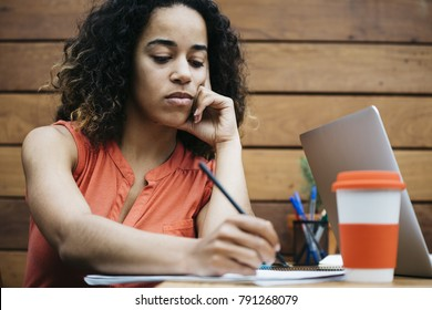 Young ethnic woman brainstorming on ideas while taking notes in notepad sitting at table in office.