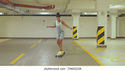 Young ethnic woman in denim overall balancing on longboard while learning to skateboard alone on empty parking.