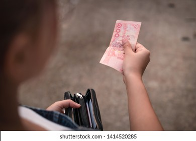 Young ethnic woman holding a red 100 baht bank note to pay for street food - Asian Thai tanned female holding a open black purse and paying with Thailand paper currency on the street