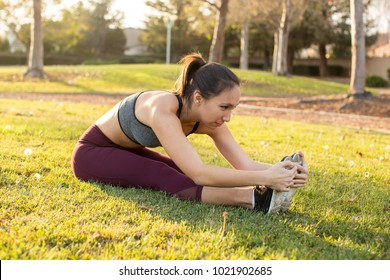 Young ethnic woman stretching for her workout