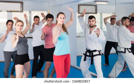 Young  european adults attempting to master new moves during karate class