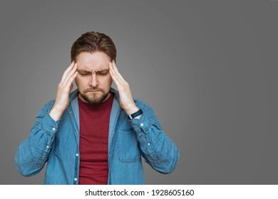 A young European bearded young man keeps his head in tension, stress, on a gray background to copy the space. Negative human emotions and feelings