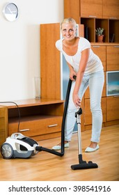 Young european blonde in casual using domestic hoover during clean-up
