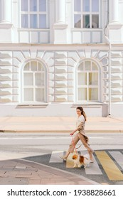 young European brunette with dog crosses the road on pedestrian crossing. spitz with mistress walks around the city. old building in the background. empty streets. world animal day
