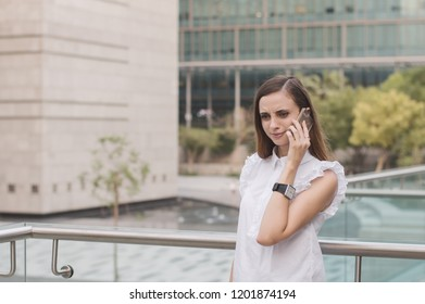 Young european business woman standing in business district and speaking via mobile phone with astonished and surprised face expression