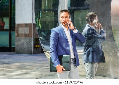 Young European Businessman with beard, little gray hair, wearing blue blazer, white shirt, gray pants, holding black leather briefcase, standing by mirror in New York City, talking on cell phone.