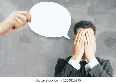 Young european businessman with covered face and thought/speech bubble on concrete background. Communication concept. Copy space