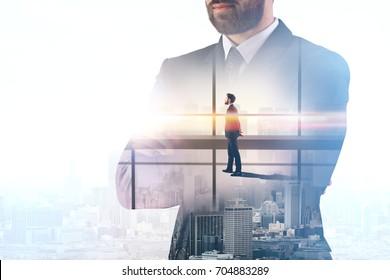 Young european businessman with folded arms standing on bright office and city background. Think concept. Double exposure