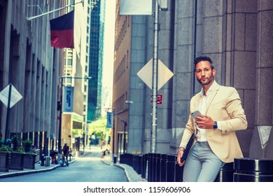 Young European Businessman traveling, working in New York City, with beard, little gray hair, wearing beige blazer, gray pants, holding briefcase, cell phone, sitting on old street, taking work break.