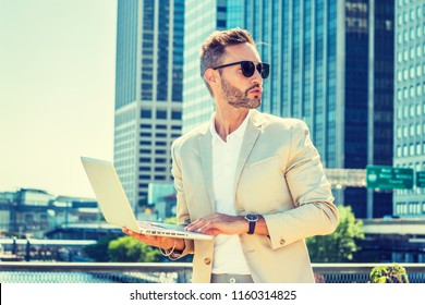 Young European Businessman traveling, working in New York City, with beard, little gray hair, wearing beige blazer, sunglasses, standing outside in business district, working on laptop computer.