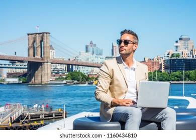 Young European Businessman traveling, working in New York, with beard, little gray hair, wearing beige blazer, sunglasses, sitting by river, working on laptop computer. Brooklyn bridge on background.