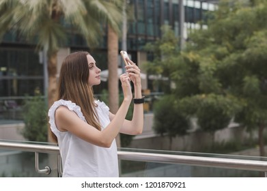Young european female with brown hair and in white casual style blouse taking photos with her mobile phone. Woman taking a selfie outdoors