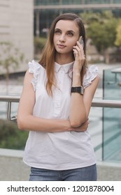 Young european female with brown hair, in white blouse and blue jeans calling via mobile phone with very concentrated and attentive face expression. Communication and mobile phone calls