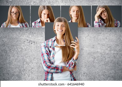 Young european female hiding herself behind poster with smiling face. Row of faces with different expressions in the background. Emotion concept
