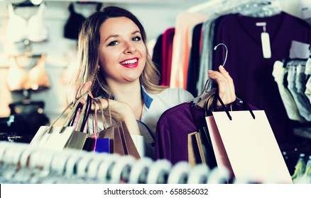 Young european female shopper examining long sleeve shirts in underwear shop