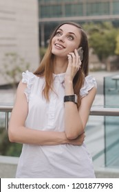 Young european female talking via mobile phone with very surprised and astonished face expression. Positive emotion. Happy and smiling face of young business woman