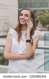 Young european female talking via a mobile phone with happy and smiling face. Successful office worker or female entrepreneur