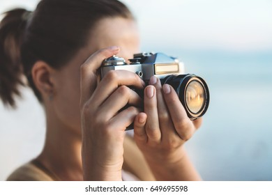 Young european female tourist taking photo of beautiful sunset at the beach with her retro camera. Mock up, copy space for your text.